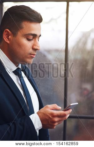 Businesslike man looking into smartphone. Arabian man chatting with business partners.Telephone, modern technology, virtual communication concept.