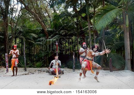 Group of Yugambeh Aboriginal warriors dance during Aboriginal culture show in Queensland Australia.