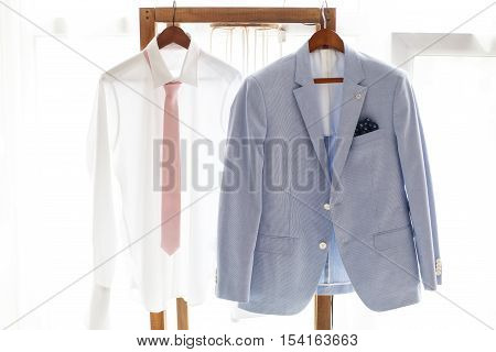White shirt with necktie and gray suit of groom hanging on hanger wedding clothing
