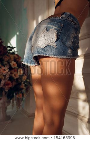 Sexy young woman legs in jeans shorts. Perfect female body, beauty, sex concept