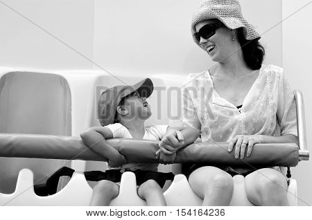 Young mother and her child little girl (age 04) ride on thrill ride in amusement park. (BW) Travel concept copyspace