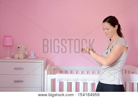 Mum Looking At Her Watch While Her Baby Sleeps