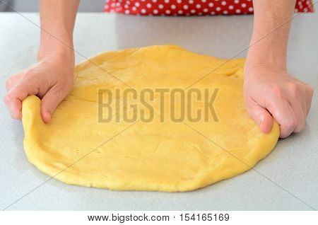 A woman kneading and stretching Pizza dough