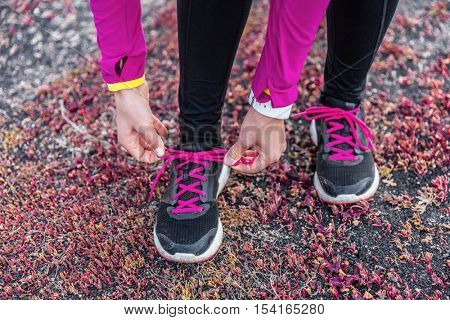 Fitness woman trail runner lacing running shoes. Athlete girl getting ready for run workout tying running shoe laces outside. Healthy lifestyle concept.