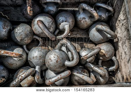 Many kettlebells weights background at outdoor gym. Texture of steel free weights for weightlifting lying on the floor at fitness center for cross training.
