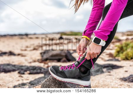 Fitness smartwatch woman runner lacing running shoes on beach, Athlete girl getting ready for run workout tying running shoe laces outside wearing watch gear. Healthy lifestyle concept.