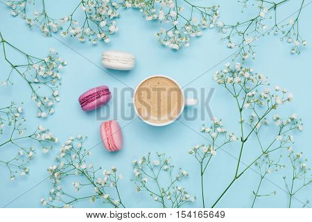 Morning cup of coffee, cake macaron and flower gypsophila on blue table from above. Cozy breakfast. Flat lay style.