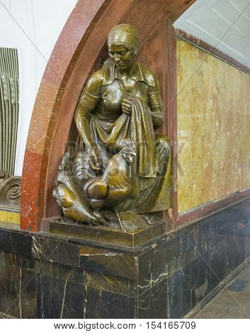 MOSCOW RUSSIA - MAY 10 2015: The bronze sculpture in Revolution Square Metro Station depicts the peasant woman feeding chickens on May 10 in Moscow.