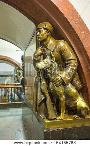 MOSCOW RUSSIA - MAY 10 2015: The bronze sculpture of a frontier guard with a dog in hall of Revolution Square Metro Station on May 10 in Moscow.