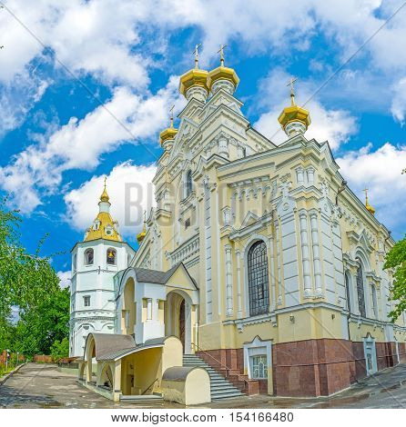 The Church of Holy Virgin Lady of Ozeriana with the golden onion domes and carved patterns on the walls Holy Virgin Monastery Kharkov Ukraine.