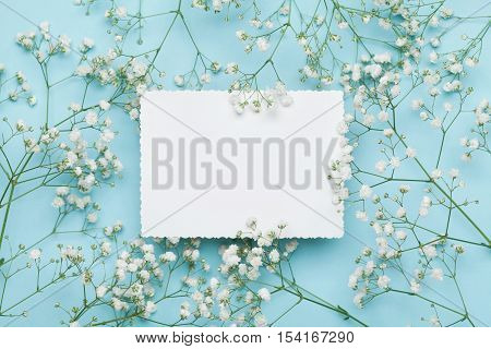 Wedding mockup with white paper list and flowers gypsophila on blue table from above. Beautiful floral pattern. Flat lay style.