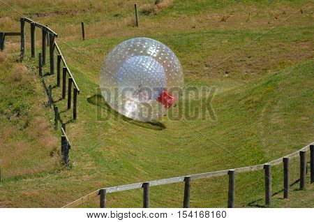 Man rides in ball rolling Zorbing in Rotorua New Zealand.