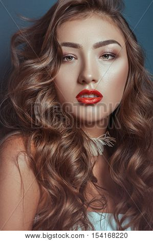 Beautiful caucasian girl with curly long hair and luxury makeup with accessories on a neck