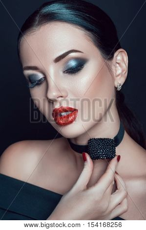 Portrait of beautiful brunette girl with evening fashion makeup and accessory on neck on black background