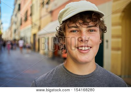 Humeral portrait of smiling teenage boy on the street.