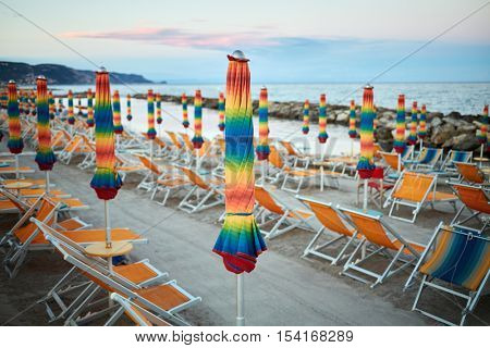Empty beach with folded umbrellas and lounges on coastline in evening.