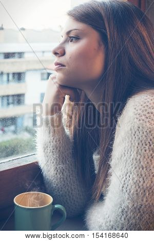 a girl with cup steaming the window