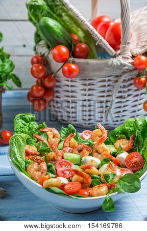 Healthy salad with vegetables and shrimp on old wooden table