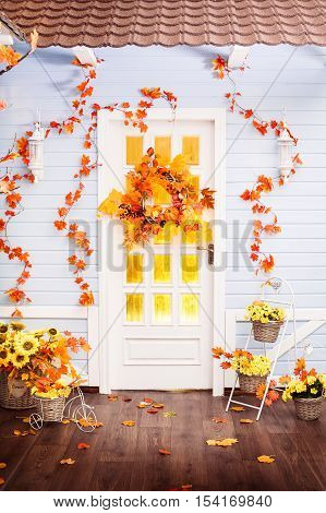 House With Tiling Roof, Blue Wooden Walls, Entwined With Autumn Leaves. Wicker Wreath Decorated With