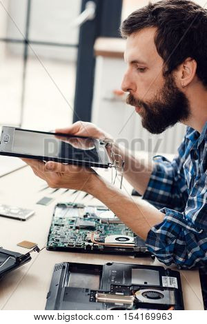 Engineer blow the dust off digital screen. Laptop disassembling in electronic repair shop. Technology renovation, occupation, business concept