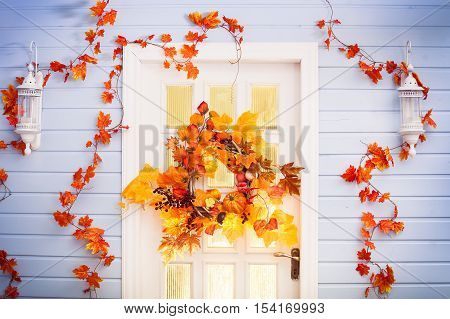 Autumn Wreath Entwined With Leaves, Garlic, Berries, Pumpkins, Mushroom, Hanging On The White Door.