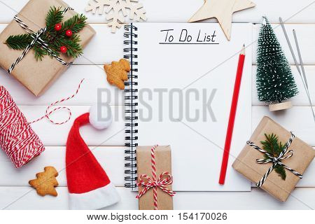 Holiday decorations, gift or present box, miniature fir tree and notebook with to do list on white wooden table from above. Christmas or winter planning concept. Flat lay style.