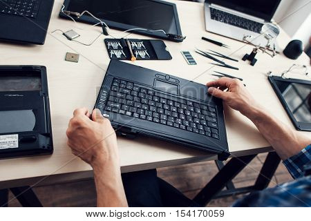 Keyboard of disassembled laptop, repairman pov. Engineer workplace with necessary tools. Electronic repair shop, business, occupation concept