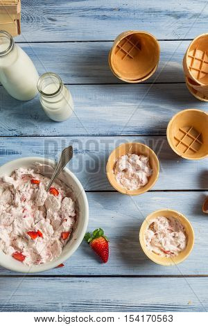 Homemade strawberry ice cream with yogurt on old wooden table