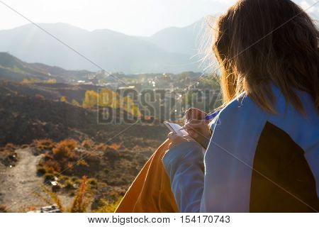 Female traveler writing her thoughts at sunset. Adventurer sitting down with pen and book.