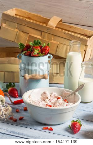 Ingredients for homemade strawberry ice cream on old wooden table