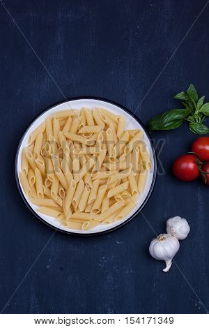 raw penne pasta and tomato, basil and garlic