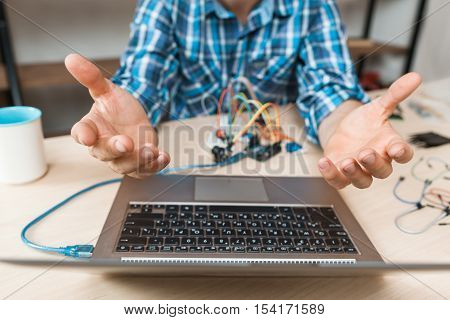Engineer hands raised up in desperate to laptop. Bored of waiting programmer talking to hovering computer. Programming, failed connection, old technology lag