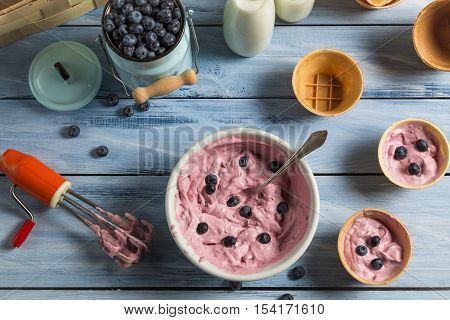 Ingredients for homemade blueberry ice cream on old wooden table