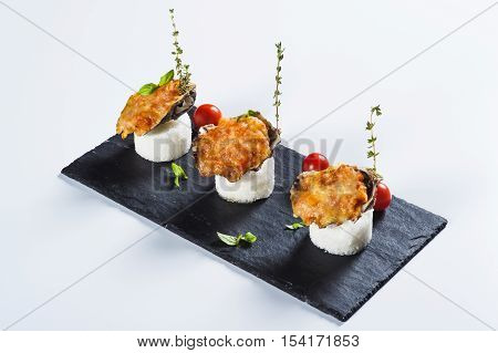 Beautifully decorated baked oyster with cheese on plate on light background