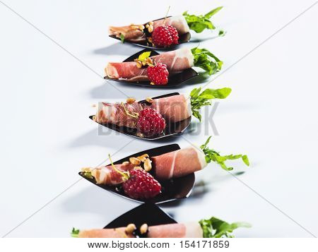 Rolled ham with arugula served with raspberrie on black plate on light background