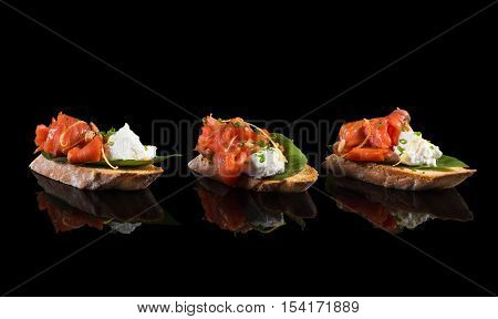 Bruschetta with salmon and soft cheese on black background