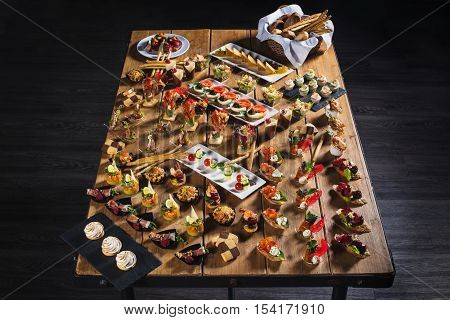 Snacks set. Brushettas canapes salads desserts tartlets oysters on wooden table wooden background