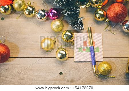 christmas card with pen surrounded by colorful baubles.