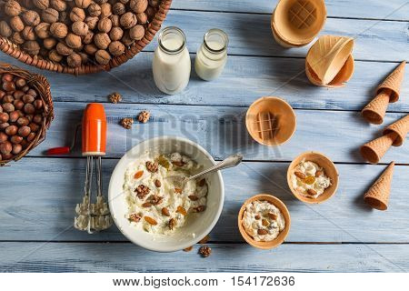 Ingredients for homemade nuts ice cream on old wooden table