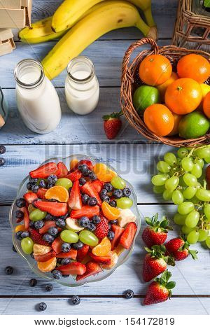 Preparing a healthy fruit salad on old wooden table