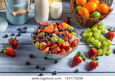 Healthy salad made of fresh fruits on old wooden table