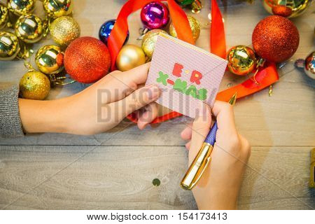 writing a greeting card for Christmas.