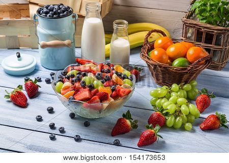 Preparing a healthy spring fruit salad on old wooden table