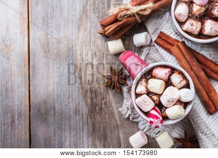 Hot chocolate with marshmallows and spices on rustic wooden table. Selective focus, tasty holidays concept. Drink for fall and winter, christmas beverage. Top view, copy space background