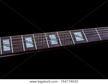 Inlay of guitar on fingerboard selective focus, on black background