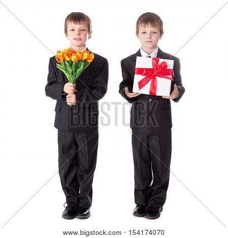 Mother's Day Concept - Two Cute Little Boys Twins In Business Suits With Flowers Ang Gift Isolated O