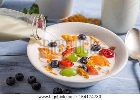 Pouring milk on cornflakes with fruits on old wooden table