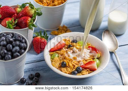 Pouring milk into cornflakes with fruits on old wooden table