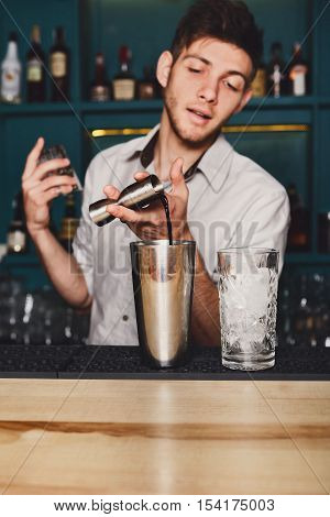 Young handsome barman in bar interior pouring alcohol to cocktail drink from measuring glass. Professional bartender at work in night club. Service industry occupation. Vertical image