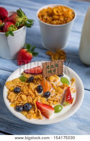 Enjoy your breakfast with cornflakes and fruits on old wooden table